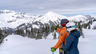 Photography of a girl and a boy with ski clothe pointing toward the snowy mountains in front of them