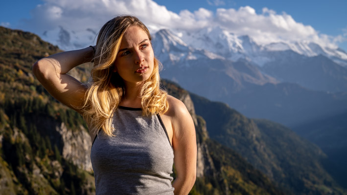 Portrait of a blond young women with blue eyes in front of the Mont-Blanc panorama in Passy (France)